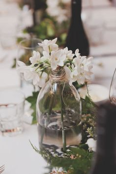 Paperwhites in a glass bottle for a winter wedding