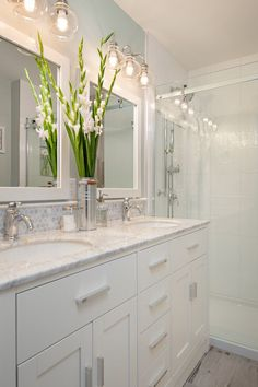 small bathroom with white cabinets under two white sinks, white wooden framed mirrors, white ceramic tiles wall in the shower area with glass partition