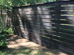 Shou sugi ban horizontal cedar fence. Used steel posts, pre-drilled and screwed each board into posts. One inch gaps between 2x6 cedar s4s boards. #torchedcedarfence #horizontaltorchedfence #cedarfence #modernfence