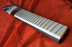 Sankey Guitars - The Archangel minimalist guitar | A unique minimalist instrument utilizing the airfoil-shaped neck cross-section. This one has frets, but that's about it. There is only cocobolo rosewood for the body and curly maple for the fretboard and bridge, tensioned with steinberger gearless tuners. A custom-designed pickup from Pete Biltoft at Vintage Vibe pickups is hidden under the bridge plate. It's hardwired through a permanent tone control for a mellow and jazzy tone.