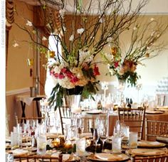 tables were topped with glass containers filled with tall curly willow branches wired with white and green dendrobium orchids and hanging gold votives. Bunches of white hydrangeas and mums lined the rims of the vases, along wit...