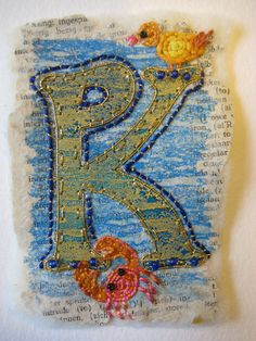 Page 4. The K fused with the P (Kiama's initials) Paper fused with felt then painted bondaweb to simulate water. The letter is painted vilene with gold painted bondaweb. Kiama was born under the water sign Cancer and loved the beach and swimming in the sea. The bird presents her spirit.