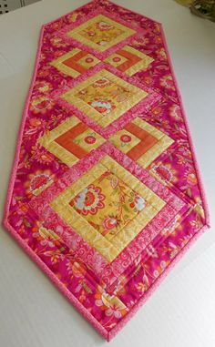 This lovely runner, for kitchen or dresser, is just in time for summer and Mothers Day. On the front, I used a group of fabrics from Moda, called High Street. This is a group of beautiful pink yellow prints. I used five fabrics from that group to make this runner. On the back, I used a pretty cherry blossom print. The binding is a sixth fabric from the High Street collection that compliments both sides. The quilting was done is simple outline stitching that looks really great on the back…
