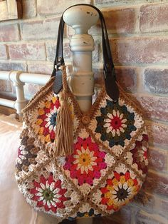 Ravelry: Sunburst Granny Square Purse I made thirteen sunburst granny squares, connecting them with a zigzag slip stitch. I added alternating front post half double crochet edging around the top and stitched on leather handles. A butt. Crochet Potholder Patterns, Crochet Tote, Crochet Handbags, Crochet Purses, Crochet Granny, Crochet Stitches, Knit Crochet, Double Crochet, Crochet Cushions