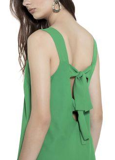Regata com alças grossas e decote em v, possui ainda duas faixas com amarração em laço no decote das costas. Essa é uma blusa básica e delicada, permite compor looks dos mais varia