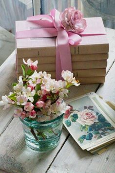 Pretty little set up of vintage books wrapped in ribbon, flowers in a glass, and vintage flower prints