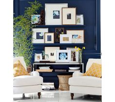 gallery of art on shelves, navy blue paint