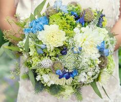 blending wedding colors in the bouquet %u2013 blue, white, green. Blue thistle, light and dark blue delphinium, white dahlias, white stock, white veronica, green hydrangea, queen annes lace, seeded euc, blue lace cap hydrangea, blue hydrangea, scabiosa pods,