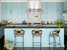 A light-blue shade on the cabinets and island complements the sea-inspired backsplash and softens stainless steel appliances and dark countertops and floors. The hint of iridescent shimmer of the tile backsplash sets off the blue cabinetry and sandy trim ceilings and inspired the color palette for the rest of the house. (Photo: J. Savage Gibson)