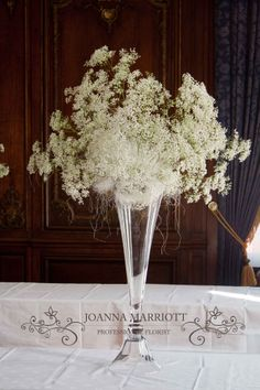 Tall vase table centre. A cloud of gypsophila arranged in glass on the foot. Winter wedding theme.