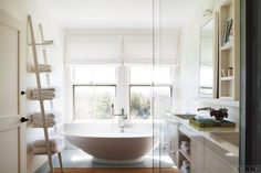For the master bath of a cotemporary Nantucket retreat, open shelving above the his-and-her sinks are accompanied by sleek cabinets below and a ladder-like piece for holding linens. Tour the home.   - ELLEDecor.com