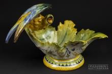 A Cantagalli maiolica bowl, formed as a large bird perched upon a leaf form bowl, decorated in Urbino style, blue cockerel painted mark, 18cm high