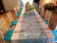 2 (8ft) Tables, White Polyester Tropical Tablecloths, Blue Sonata Runners, Turquoise Crepe Back Satin Cushion, Silver Flatware, and White Chaivari Chairs