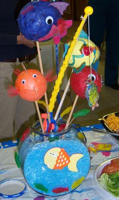 For a fish theme party I made paper mache fish and decorated them. The base is a fish bowl filled with floral snow and tinted with food coloring to simulate water. I also added a plastic fishing pole and gummy worms for a more realistic effect.