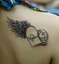 Red Ink Heart With Angel Wing Tattoo On Right Back Shoulder (Smaller) Letter M with dates on an angle below each side of the heart 5-29-71 going down by the M and 2-06-15 going up the side. Some royal blue shading in the wing maybe for her favorite color??