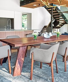 The splayed-legged dining table, designed by Christian Woo, is composed of steel and American walnut and surrounded by De la Spada chairs. The bamboo and silk rug is custom through Woven Concepts.