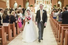 Bride and groom processing from altar after their ceremony at St. Theresa's in Ashburn.  Morning suit, yellow tie.  Bouquet with pink, red and purple roses.