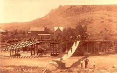 Boulder Creek-Flood - Located at the base of Boulder Canyon This foot bridge was the only way across Boulder Creek during the flood of 1894. Also note the Railroad bridge, which is under repair. REPRODUCTIONS