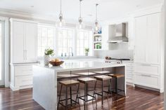 L shaped kitchen features clear glass globe pendants illuminating white marble waterfall island accented with stainless steel cabinets lined with wood and iron counter stools.