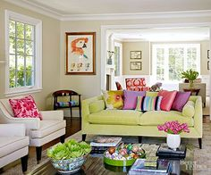 A lime green couch decorated with bright sherbet-color pillows makes this living room truly stand out. Neutral walls, chairs, and an area rug balance the splashy couch and pillows. When incorporating lots of bright, bold colors, keep balance and scale in mind so the space doesn't come across as over-the-top./