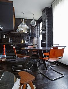 Chrome and curvy Mies van der Rohe cantilevered chairs in a seasoned tan leather are great with this black interior.