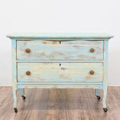 This shabby chic dresser is featured in a solid wood painted in a distressed light blue and yellow chalk paint. This small antique dresser is in great condition with 2 large drawers, a rolling wheel base and curved trim top. Eclectic storage piece!   #shabbychic #dressers #shortdresser #sandiegovintage #vintagefurniture