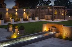 Mood lighting creates a chic atmosphere in a contemporary garden featuring a cor-ten steel water feature and a modern pergola