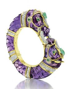Amethyst, emerald and diamond bangle bracelet by David Webb. The carved amethyst hinged bangle designed as two opposing horses, with circular-cut diamond detail and cabochon emerald accents, mounted in 18k gold and platinum.