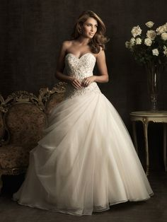 Allue: 8901	A fabulous ball gown with tons of sparkle. The fitted bodice is adorned with embroidery and Swarovski crystals and features a strapless sweetheart neckline. The full ball gown skirt is constructed from soft tulle that drapes asymmetrically to create a romantic silhouette.