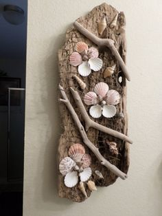 Beautiful decorative driftwood and shells wall art sculpture. This one-of-a-kind ocean themed wall decor is beautifully decorated driftwood with gorgeous shells accented with netting to created a wonderful masterpiece! Has hook for hanging. This large driftwood art sculpture would