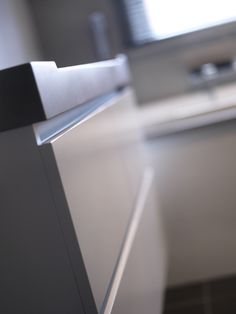 Close up of Assenti craftmen ship. Solid surface countertop in concrete light combined with matte white base cabinet.
