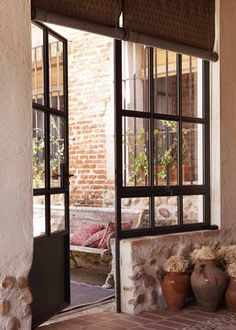 Wise use of window and door to allow light in. Love the stone and pottery Steel Doors And Windows, Metal Windows, Casa Loft, Casa Patio, Patio Interior, Paint Colors For Home, Garden Styles, My Dream Home, Dream Homes
