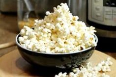 a black bowl of popped popcorn made in an instant pot.