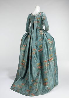 Robe à la Français (1760–70), made of silk and cotton.  The silhouette, composed of a funnel-shaped bust feeding into wide rectangular skirts and allowed for expansive amounts of textiles with delicate Rococo curvilinear decoration.  The robes à la française are renowned for the beauty of their textiles, the cut of the back employing box pleats and skirt decorations, known as robings, which showed endless imagination and variety.