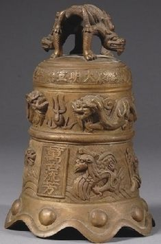 A 19th century (circa 1801-1900) Chinese bronze bell with dragon finials, carved surface, Qing dynasty,12 inches. The surface is carved with various types of dragons and pearls, and the Xuan De (Hsuan Te) mark at the shoulder.