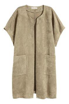 Abrigo corto: Abrigo corto en ante sintético con mangas cortas y holgadas, tira de atar en la cintura y bolsillos delanteros. Sin cierre ni forro.
