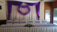 Esküvői főasztal és háttere. Lila és krém virágos főasztaldísz, indamintás organza asztali futó, fehér székszoknya lila masnival, fehér és lila háttérdekorációs anyag lila lufiszívvel.