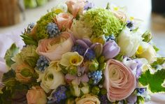 Pastel spring flower brides bouquet in a compact style. Ranunculus, freesia, tulips, viburnum, for-get-me-nots, scented narcissus, peach spray roses, pipped hyacinths and muscari.