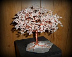 Pearlescent seed bead and copper wire tree on slate.