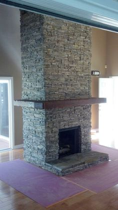 Stacked stone and hand made mantle to looked like distressed lumber.