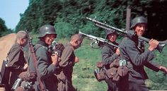 Rare color photos of a marching German column, with two Soviet POW carrying items for them.  The Soviet POWs seem to be  young and healthy, but downcast.