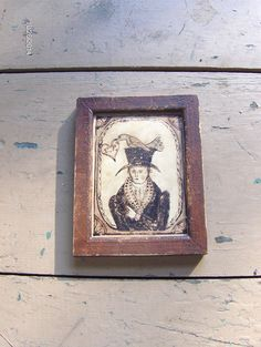"Early style watercolor Valentine of a Gentleman pointing to a bird on his hat grasping a heart with initials.  in a grungy painted frame, 3"" X 4"".  By Steve Shelton."