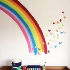 Some tester pots of paint for the rainbow some card cutouts of butterflies painted with leftover paint, some Blu-tack to stick the butterflies to the wall. Cheap but effective wall mural! Rainbow Bedroom, Rainbow Nursery, Rainbow Wall, Rainbow Room Kids, Rainbow Butterfly, Unicorn Rooms, Unicorn Bedroom, Butterfly Bedroom, Rainbow Painting