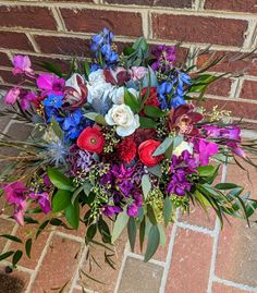 Jewel toned boho styled bouquet with fuschia and burgundy orchids, blue delphinium, deep coral ranunculus, blue eryngium, purple stock and more with eucalyptus and ruscus greenery.