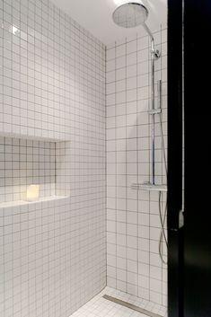 Espace de douche carrelé blanc avec un pommeau de douche fixé au mur