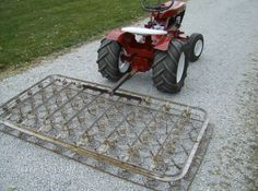 """This homemade (from an old bed spring) gravel leveler/smoother is one piece of """"redneck equipment"""" illustrated Garden Tractor Attachments, Atv Attachments, Gravel Driveway, Driveway Landscaping, Farm Tools, Garden Tools, Wheel Horse Tractor, Yard Tractors, Landscape Rake"""