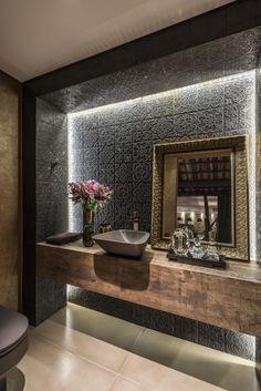 Lavabo, bancada de madeira, espelho com moldura, ladrilho, castelatto, granito preto, moldura dourada, cuba de apoio, iluminação