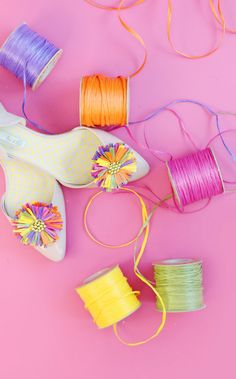 Hot glue a raffia pom pom to a shoe clip to cover any pair of flats or heels in…