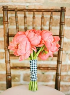 A bouquet of coral peonies wrapped in navy + white gingham.