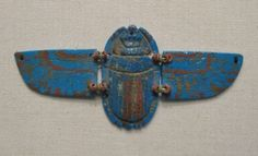 A large winged scarab made from polychrome faience. Late Dynastic Period (664-323 BC). Large winged examples were often placed on the chest of the mummified deceased or wrapped inside the bandages over that part of the body. The Late Dynastic Period saw a continuation of the extraordinarily high quality of faience production that characterized the earlier Third Intermediate Period. This example in blue, red and yellow faience, is made from 3 parts: the scarab beetle itself ...